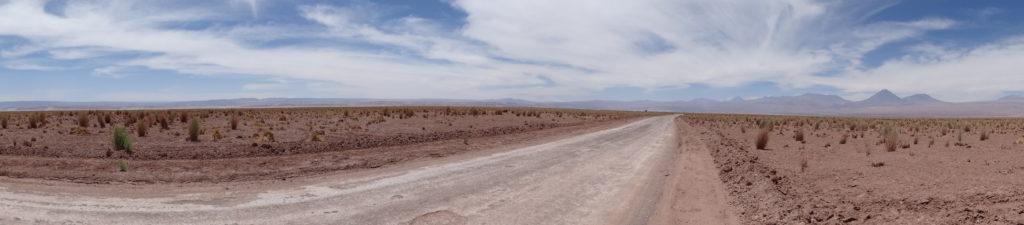 Eine Panoramenaufnahme von West (links) nach Ost (rechts). Im Osten erheben sich die bis zu 6000 m hohen Vulkangipfel der Andenkordillere. Die höchsten Erhebungen der Domeyko-Kordillere im Westen erreichen ~4.000 m Höhe.