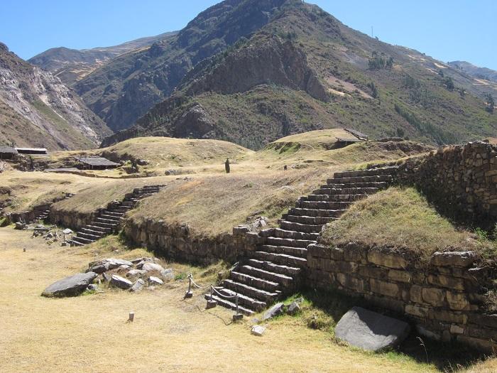 Die Mauern der Ruine Chavín de Huantar sind mit Gras überwachsen.